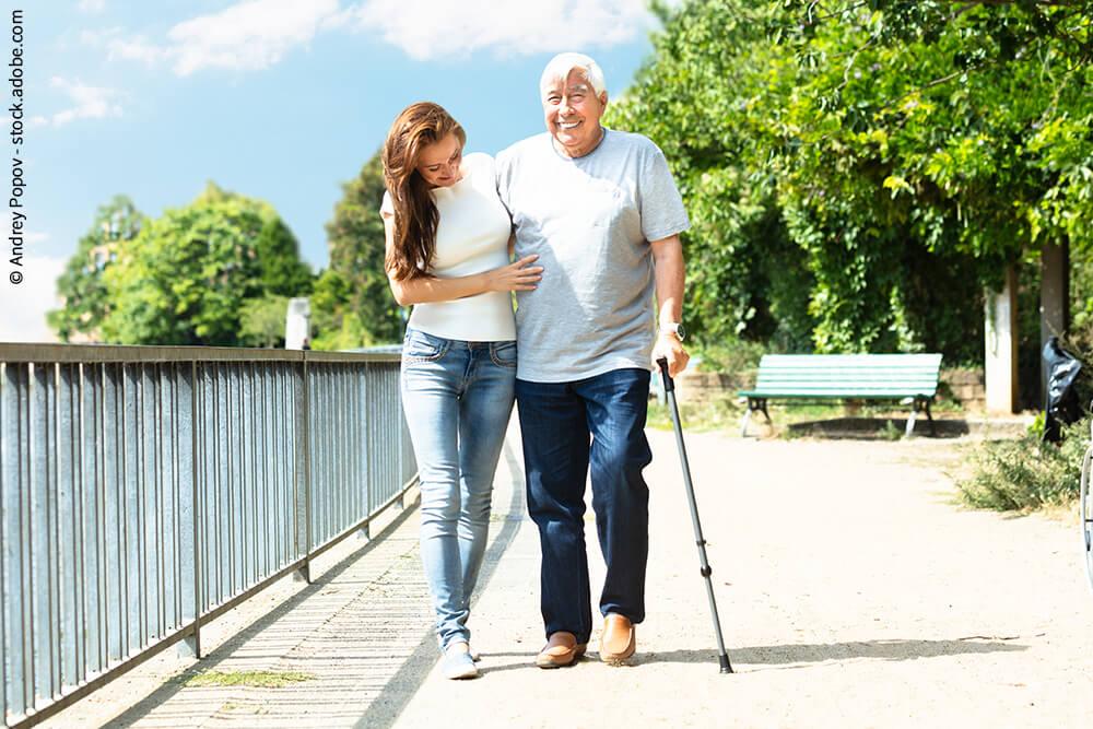 Frau unterstützt Senior beim gehen
