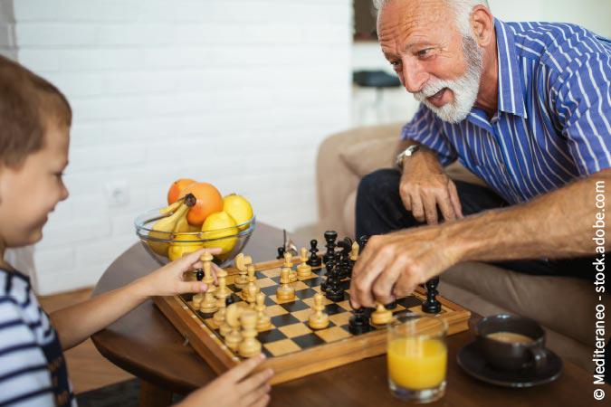 Senior spielt mit Enkel Schach